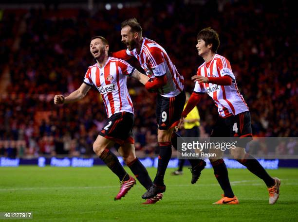 Phil Bardsley of Sunderland celebrates with team mates Steven Fletcher and Ki SungYong as Ryan Giggs of Manchester United scores an own goal during...