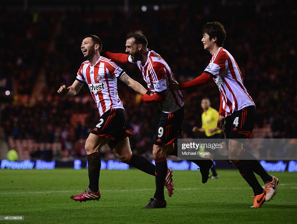 Phil Bardsley of Sunderland (L) celebrates with team mates Steven Fletcher (C) and Ki Sung-Yong (R) as Ryan Giggs of Manchester United (not pictured) scores an own goal during the Capital One Cup Semi-Final, first leg match between Sunderland and Manchester United at Stadium of Light on January 7, 2014 in Sunderland, England.