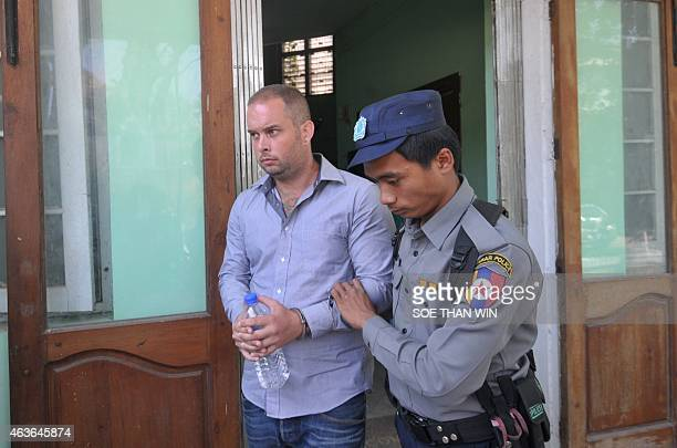 Phil Blackwood a bar manager from New Zealand escorted by police leaves the court after a hearing in Yangon on February 17 2015 Blackwood is accused...
