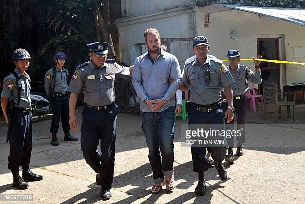 Phil Blackwood a bar manager from New Zealand is escorted by police as he arrives at a court for a hearing in Yangon on January 2 2015 Blackwood is...