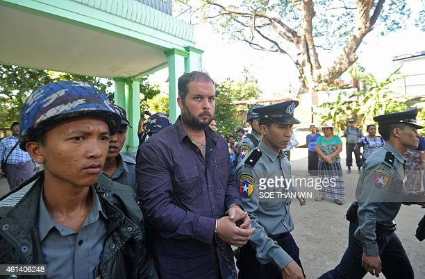 Phil Blackwood a bar manager from New Zealand is escorted by police as he leaves the court after a hearing in Yangon on January 12 2015 Blackwood is...