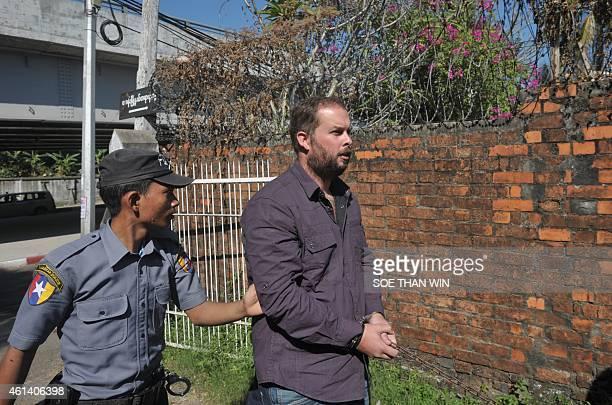 Phil Blackwood a bar manager from New Zealand is escorted by police as he arrives at a court for a hearing in Yangon on January 12 2015 Blackwood is...