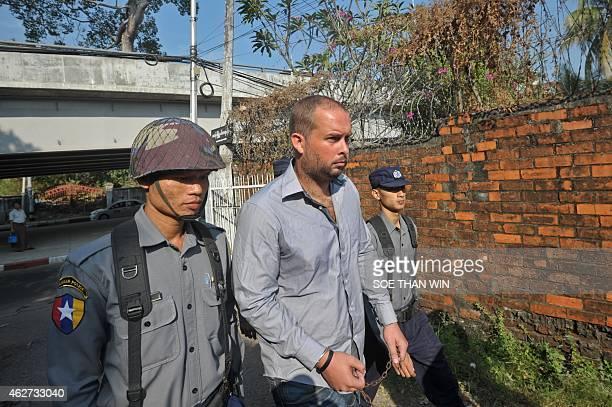 Phil Blackwood a bar manager from New Zealand is escorted by police as he arrives at a court for a hearing in Yangon on February 4 2015 Blackwood is...
