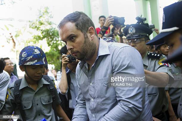 Phil Blackwood a New Zealand bar manager is guarded by police as he attends a court hearing in Yangon on December 26 2014 Blackwood is accused of...