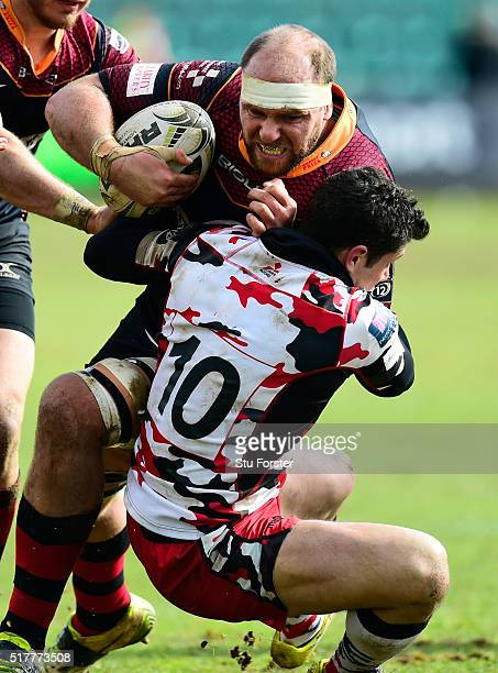Phil Burleigh of Edinburgh tackles Dragons player Cory Hill during the Guinness Pro 12 match between Newport Gwent Dragons and Edinburgh Rugby at...