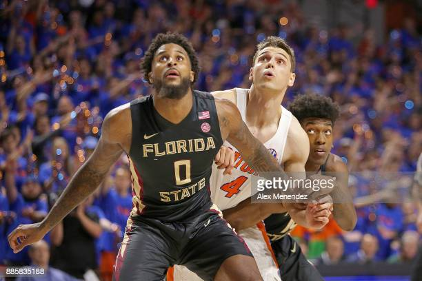 Phil Cofer and Terance Mann of the Florida State Seminoles block out Egor Koulechov of the Florida Gators during a NCAA basketball game at the...
