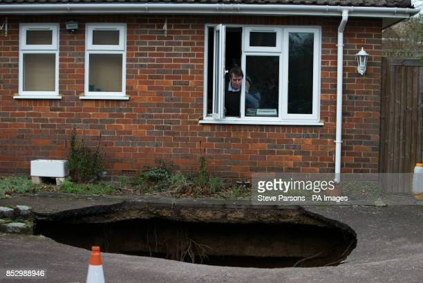 Phil Conran looks out of a window from his home in Main Road Walter's Ash High Wycombe Buckinghamshire after a 30ftdeep sinkhole opened up in the...