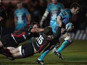 Phil Dollman of Exeter Chiefs bursts through the tackles of Martyn Thomas and Robert Sidoli of Newport Gwent Dragons during the Amlin Challenge Cup...