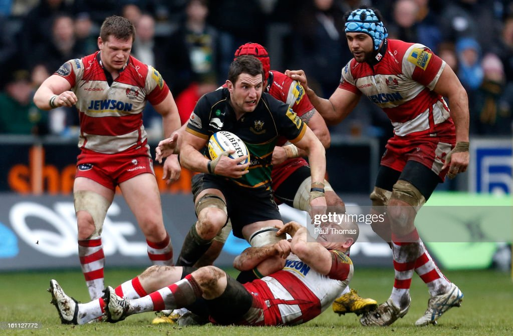 <a gi-track='captionPersonalityLinkClicked' href=/galleries/search?phrase=Phil+Dowson&family=editorial&specificpeople=226672 ng-click='$event.stopPropagation()'>Phil Dowson</a> (C) of Northampton is tackled by <a gi-track='captionPersonalityLinkClicked' href=/galleries/search?phrase=Mike+Tindall&family=editorial&specificpeople=204210 ng-click='$event.stopPropagation()'>Mike Tindall</a> of Gloucester during the Aviva Premiership match between Northampton Saints and Gloucester at Franklins Gardens on February 9, 2013 in Northampton, England.