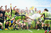 Phil Dowson of Northampton Saints dives in front of his team mates as they celebrate with the trophy after the Aviva Premiership Final between...