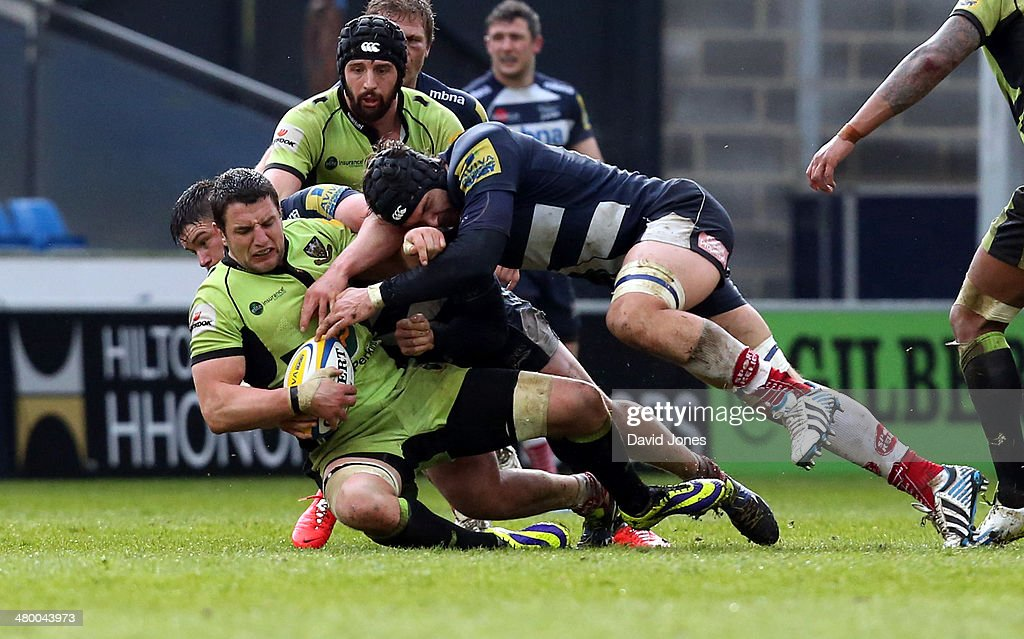 Phil Dowson of Northampton Saints is tackled by Andrei Ostrikov of Sale Sharks during the Aviva Premiership match between Sale Sharks and Northampton Saints at A J Bell Stadium on March 22, 2014 in Salford, England