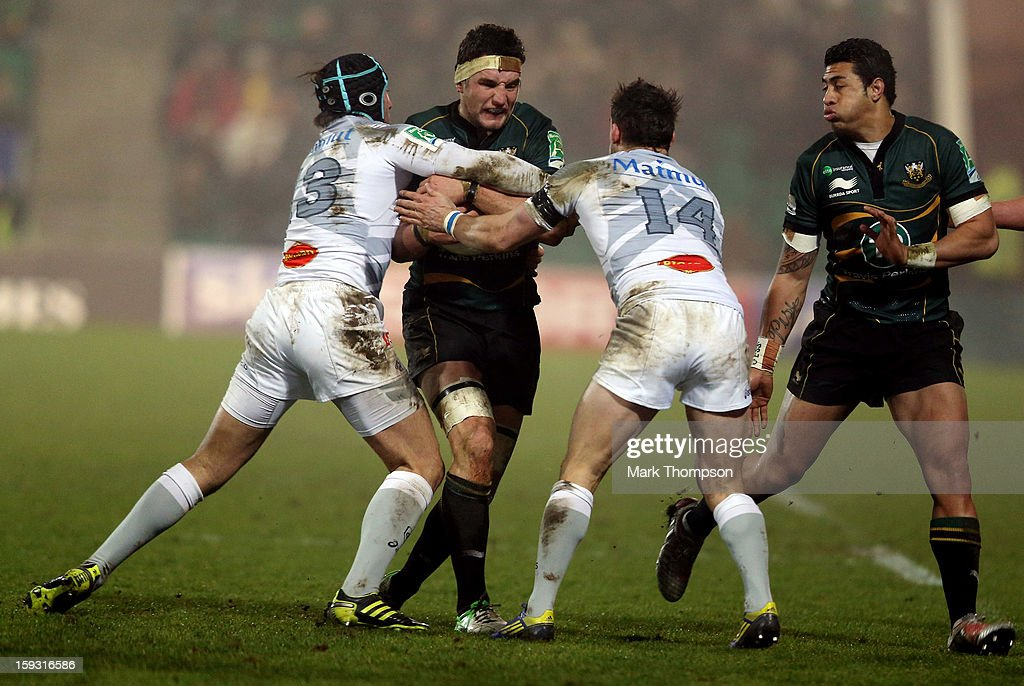 <a gi-track='captionPersonalityLinkClicked' href=/galleries/search?phrase=Phil+Dowson&family=editorial&specificpeople=226672 ng-click='$event.stopPropagation()'>Phil Dowson</a> of Northampton Saints tangles with Maxwell Evans and Anton Peikrishvili of Castres Olympique during the Heineken Cup match between Northampton Saints and Castres Olympique at Franklin's Gardens on January 11, 2013 in Northampton, England.