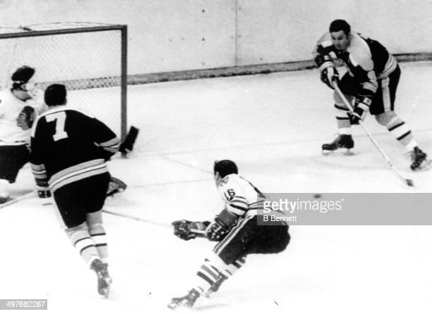 Phil Esposito passes to John Bucyk of the Boston Bruins to score against goalie Tony Esposito of the Chicago Blackhawks as Chico Maki of the...
