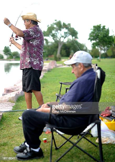 Phil Gallegos left casts the fishing pole for his dad Jose Gallegos on Thursday June 14 2012 as they go fishing with Phil's wife Claudia in...