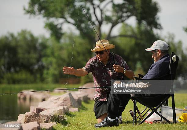 Phil Gallegos left prepares the fishing pole for his dad Jose Gallegos on Thursday June 14 2012 as they go fishing with Phil's wife Claudia in...