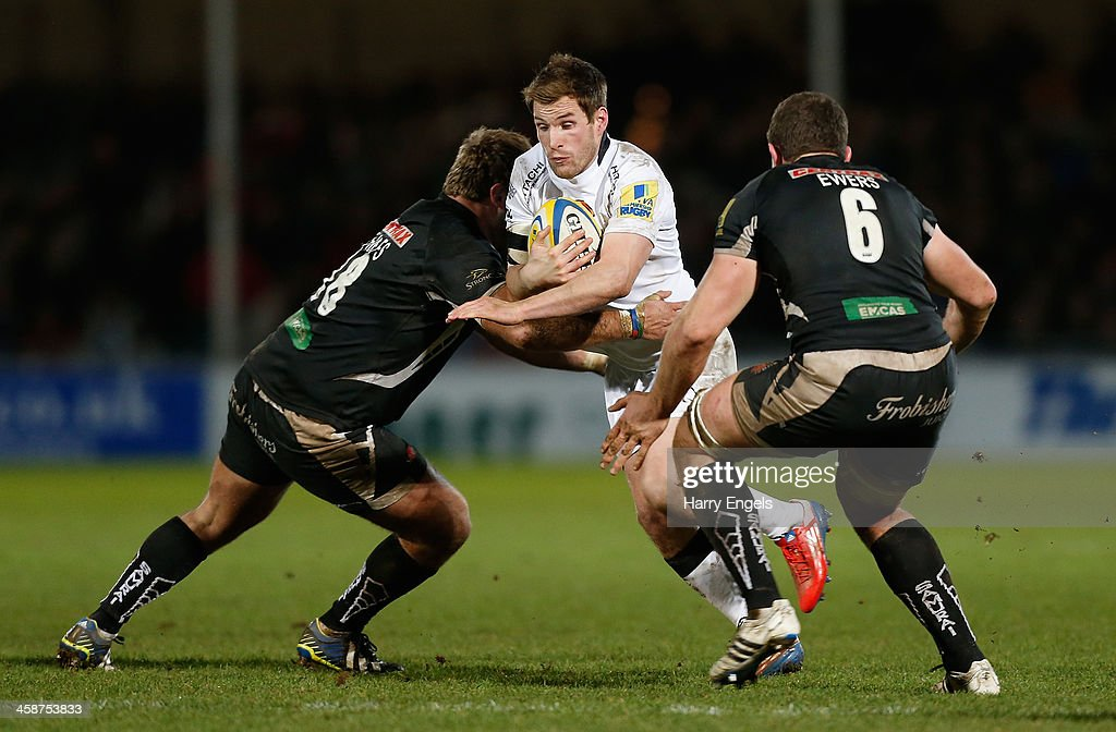 Phil Godman of Newcastle is tackled by Alex Brown and Dave Ewers of Exeter during the Aviva Premiership match between Exeter Chiefs and Newcastle...