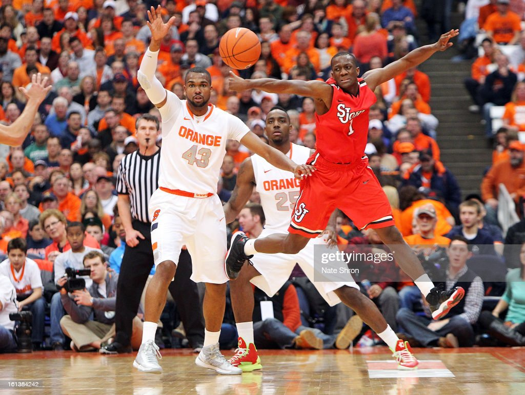 Phil Greene #1 of the St. John's Red Storm jumps up as he reaches for the ball against James Southerland #43 and Rakeem Christmas #25 of the Syracuse Orange during the game at the Carrier Dome on February 10, 2013 in Syracuse, New York.