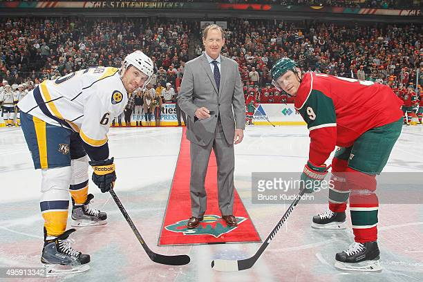 Phil Housley is honored before the game with a ceremonial puck drop with captains Shea Weber of the Nashville Predators and Mikko Koivu of the...
