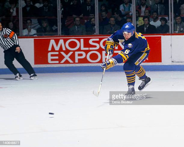 Phil Housley of the Buffalo Sabres passes the puck up the rink during a game against the Montreal Canadiens Circa 1980 at the Montreal Forum in...