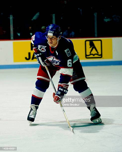 Phil Housley of the Winnipeg Jets stands at the faceoff circle during a game against the Montreal Canadiens in 1991 at the Montreal Forum in Montreal...