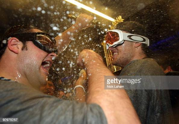 Phil Hughes and Joba Chamberlain of the New York Yankees celebrate with champagne and the trophy in the locker room after their 73 win against the...