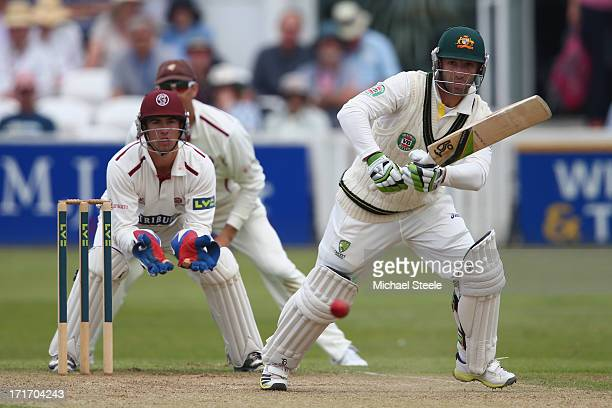 Phil Hughes of Australia plays straight as wicketkeeper Alex Barrow and Marcus Trescothick of Somerset look on during day three of the Somerset...