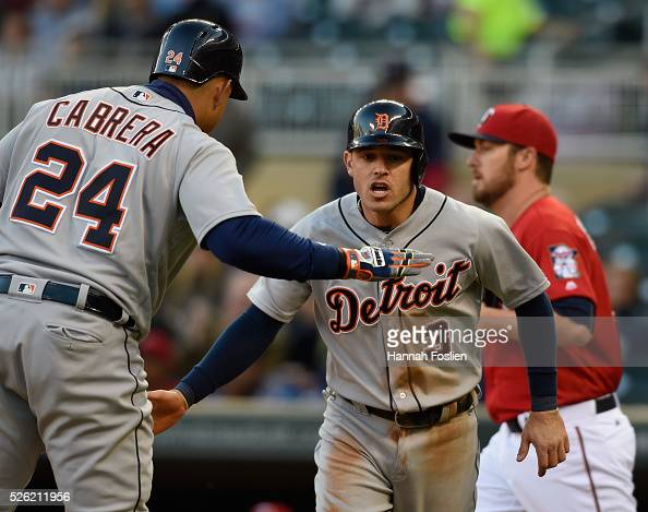 Phil Hughes of the Minnesota Twins looks on as Miguel Cabrera of the Detroit Tigers congratulates teammate Ian Kinsler on scoring a run during the...