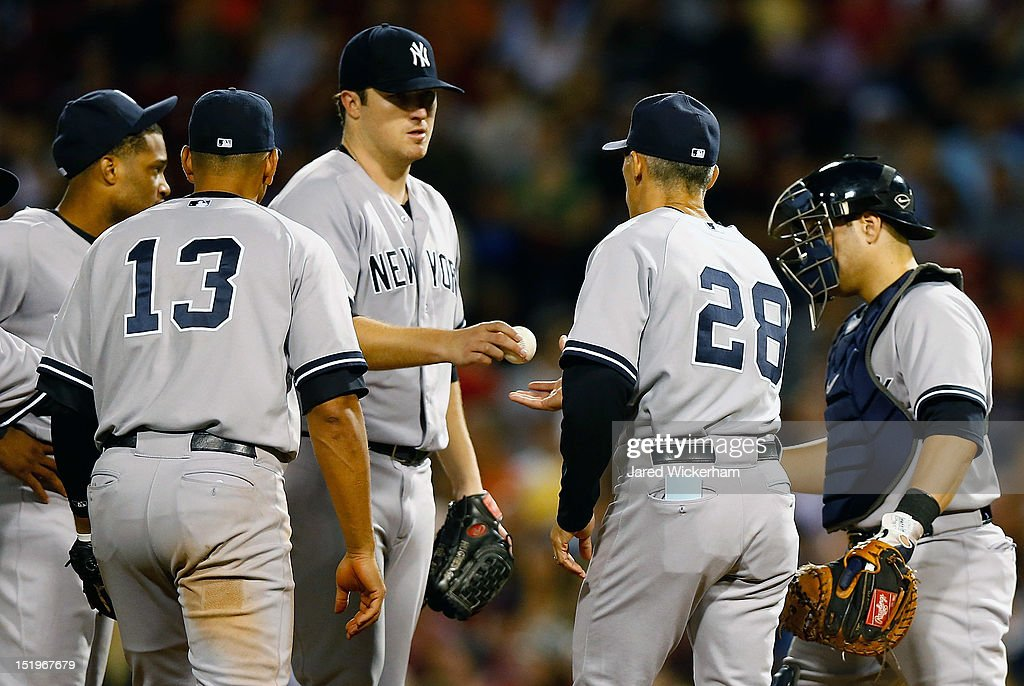 Phil Hughes #65 of the New York Yankees is pulled from the game by manager <a gi-track='captionPersonalityLinkClicked' href=/galleries/search?phrase=Joe+Girardi&family=editorial&specificpeople=208659 ng-click='$event.stopPropagation()'>Joe Girardi</a> #28 in the 8th inning against the Boston Red Sox during the game on September 13, 2012 at Fenway Park in Boston, Massachusetts.