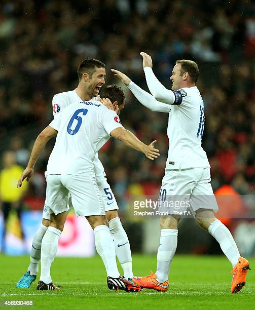 Phil Jagielka of England is congratulated by teammates Gary Cahill and Wayne Rooney after scoring the opening goal during the EURO 2016 Qualifier...