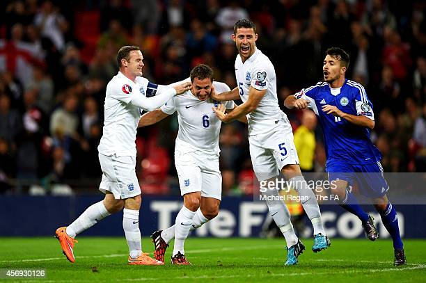 Phil Jagielka of England is congratulated by teammates Wayne Rooney and Gary Cahill after scoring the opening goal during the EURO 2016 Qualifier...