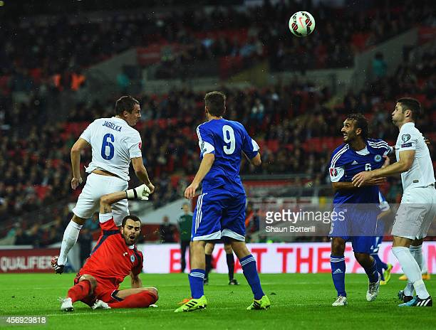 Phil Jagielka of England outjumps goalkeeper Aldo Simoncini of San Marino to score their first goal during the EURO 2016 Group E Qualifying match...