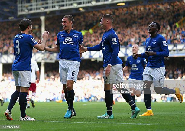 Phil Jagielka of Everton celebrates with team mates after scoring the opening goal during the Barclays Premier League match between Everton and Aston...