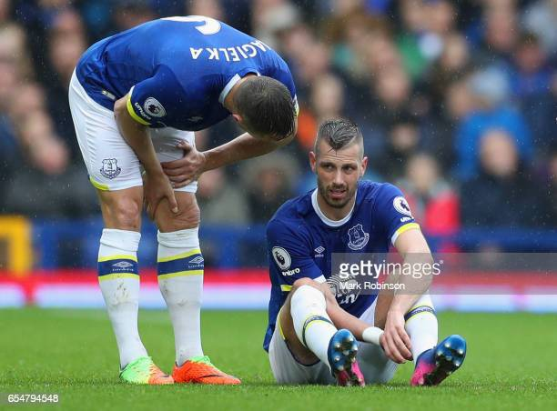 Phil Jagielka of Everton talks to injured team mate Morgan Schneiderlin of Everton during the Premier League match between Everton and Hull City at...