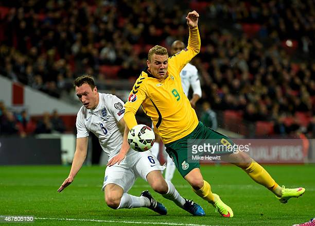 Phil Jones of England tackles Deivydas Matulevicius of Lithuania in the penalty area during the EURO 2016 Qualifier match between England and...