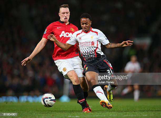 Phil Jones of Manchester United competes with Raheem Sterling of Liverpool during the Capital One Cup Third Round match betwen Manchester United and...
