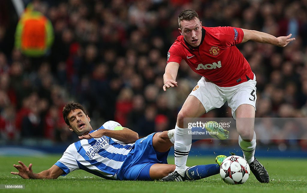 Phil Jones of Manchester United in action with Xabi Prieto of Real Sociedad scoring an own-goal during the UEFA Champions League Group A match between Manchester United and Real Sociedad at Old Trafford on October 23, 2013 in Manchester, England.
