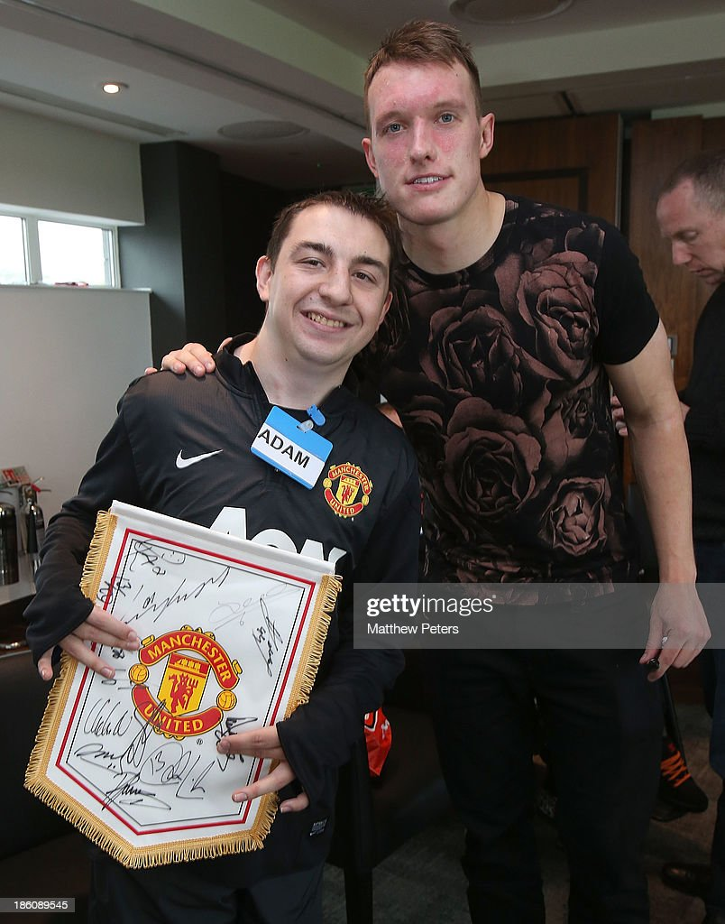 Phil Jones of Manchester United meets Adam Calow at a Manchester United Foundation Dream Day, for fans with life-limiting illnesses, at Aon Training Complex on October 28, 2013 in Manchester, England.