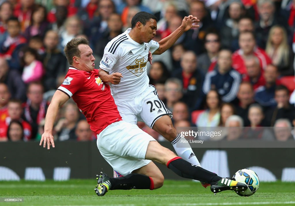 Phil Jones of Manchester United tackles Jefferson Montero of Swansea City during the Barclays Premier League match between Manchester United and Swansea City at Old Trafford on August 16, 2014 in Manchester, England.