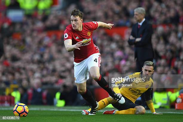 Phil Jones of Manchester United takes the ball past Aaron Ramsey of Arsenal during the Premier League match between Manchester United and Arsenal at...