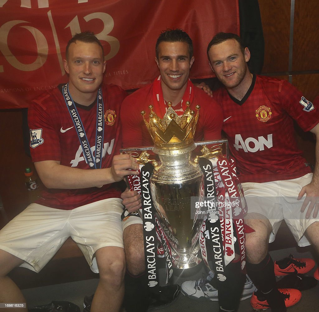 Phil Jones, Robin van Persie and <a gi-track='captionPersonalityLinkClicked' href=/galleries/search?phrase=Wayne+Rooney&family=editorial&specificpeople=157598 ng-click='$event.stopPropagation()'>Wayne Rooney</a> of Manchester United celebrate with the Barclays Premier League trophy in the dressing room after the Barclays Premier League match between Manchester United and Swansea at Old Trafford on May 12, 2013 in Manchester, England.