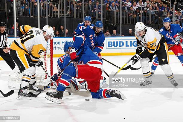 Phil Kessel and Evgeni Malkin of the Pittsburgh Penguins battle for the puck against Brady Skjei of the New York Rangers at Madison Square Garden on...