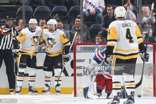 Phil Kessel Bryan Rust and Justin Schultz of the Pittsburgh Penguins celebrate after scoring a goal in the first period against Henrik Lundqvist of...