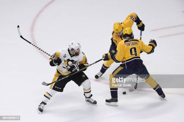 Phil Kessel of the Pittsburgh Penguins battles for the puck with Filip Forsberg and Pontus Aberg of the Nashville Predators during the second period...