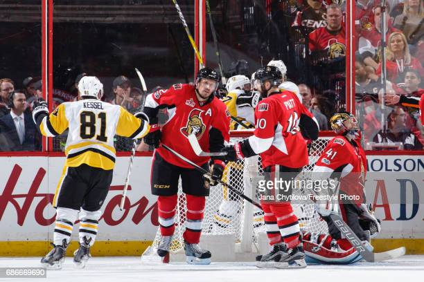 Phil Kessel of the Pittsburgh Penguins celebrates a second period powerplay goal by teammate Sidney Crosby as Dion Phaneuf Craig Anderson and Tom...
