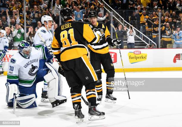 Phil Kessel of the Pittsburgh Penguins celebrates his third period goal with Evgeni Malkin against the Vancouver Canucks at PPG Paints Arena on...