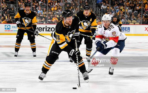 Phil Kessel of the Pittsburgh Penguins handles the puck against Jared McCann of the Florida Panthers at PPG Paints Arena on October 14 2017 in...