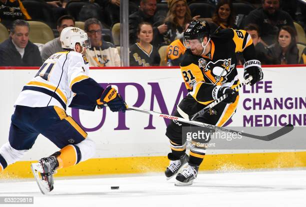 Phil Kessel of the Pittsburgh Penguins handles the puck against Mattias Ekholm of the Nashville Predators at PPG Paints Arena on January 31 2017 in...