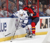 Phil Kessel of the Toronto Maple Leafs and Filip Kuba of the Florida Panthers tangle during the second period behind the net at the BBT Center on...