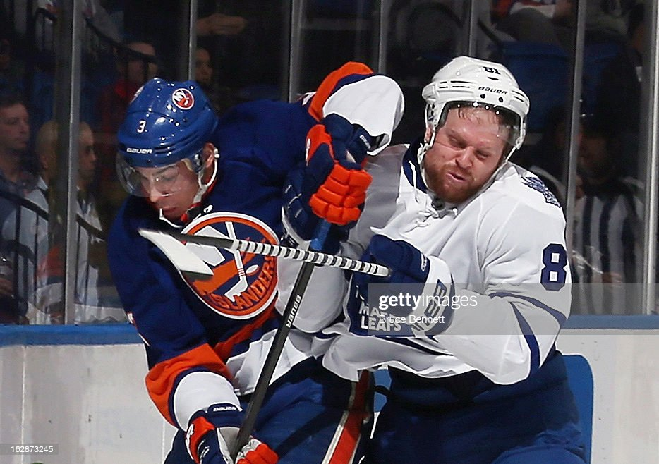 Phil Kessel #81 of the Toronto Maple Leafs hits Travis Hamonic #3 of the New York Islanders in the first period at the Nassau Veterans Memorial Coliseum on February 28, 2013 in Uniondale, New York.