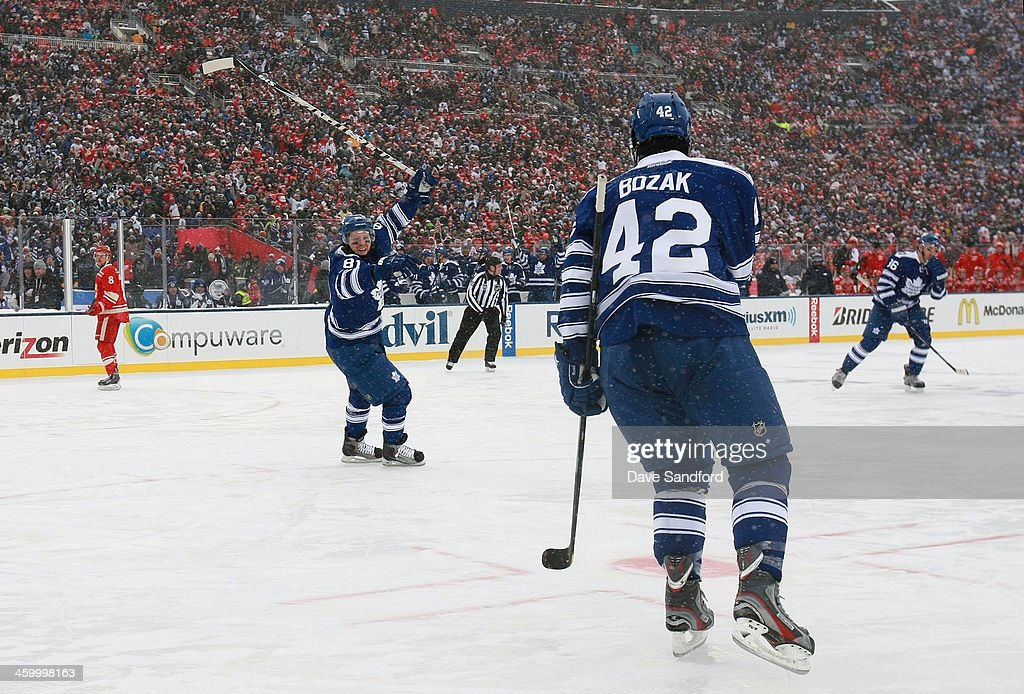 Phil Kessel #81 of the Toronto Maple Leafs reacts after teammate Tyler Bozak #42 of the Toronto Maple Leafs scored a goal in the third period as Justin Abdelkader #8 of the Detroit Red Wings looks on during the 2014 Bridgestone NHL Winter Classic on January 1, 2014 at Michigan Stadium in Ann Arbor, Michigan.